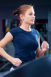 Young woman at the gym run on on a machine Stock Images