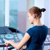Young woman at the gym run on on a machine Stock Photography