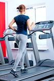 Young woman at the gym run on on a machine Royalty Free Stock Image
