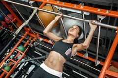 Young woman in gym sporty lifestyle pulling up on horizontal bar bottom view stock photos