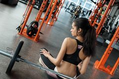 Young woman in gym sporty lifestyle sitting in lotus pose near barbell thoughtful royalty free stock photos