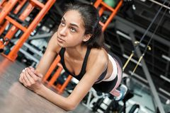 Young woman in gym sporty lifestyle standing on arms feet in suspansion straps doing plank thoughtful royalty free stock photos