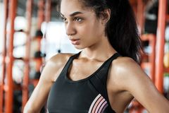 Young woman in gym sporty lifestyle standing close-up sweaty confident stock photography