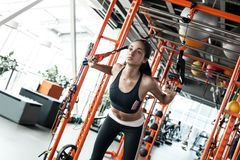 Young woman in gym sporty lifestyle total resistance workout doing back exercise with suspansion straps. Young girl in gym sporty lifestyle concept total royalty free stock images