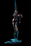 Young woman gymnast with blue gymnastic aerial silks Stock Image
