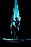 Young woman gymnast with blue gymnastic aerial silks. Isolated on black Royalty Free Stock Photos