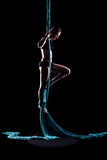 Young woman gymnast with blue gymnastic aerial silks Royalty Free Stock Photography