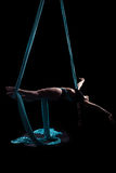 Young woman gymnast with blue gymnastic aerial silks Royalty Free Stock Image