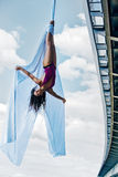 Young woman gymnast. On city and sky background Stock Images