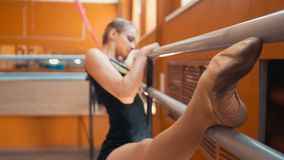 Young woman gymnast doing stretching leg on barre in a studio. Close up Stock Image
