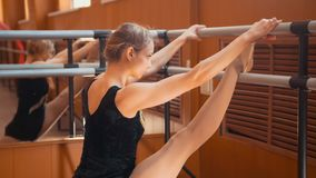 Young woman gymnast doing stretching leg on barre in a studio. Close up Royalty Free Stock Photos