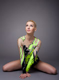Young woman in gymnast suit posing on grey Stock Image