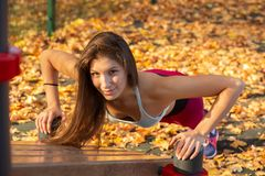Sports woman push-up. Young woman gymnast training on the autumn sports ground, push-up stock images