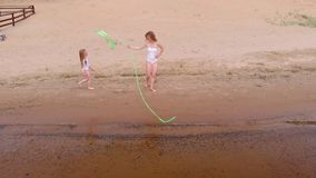 Young woman gymnast in a white body on a sandy beach dancing with gymnastic ribbon. Summer, dawn stock video footage