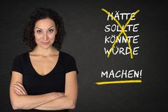 Young woman & `hätte, sollte, könnte, würde, machen` text in a blackboard. Translation: `would have, sho stock image