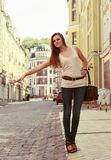 Young Woman Hailing a Cab. On the Urban Street Royalty Free Stock Image