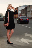Young fashion woman in black coat walking on city street Royalty Free Stock Photos