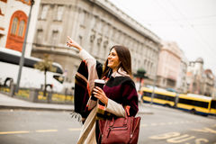 Young woman hailing a taxi on the street in the city Stock Photo