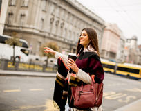 Young woman hailing a taxi on the street in the city. View at young woman hailing a taxi on the street in the city Stock Images