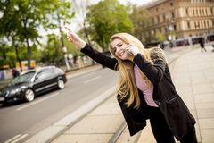 Young woman hailing a taxi on the street in the city. View at young woman hailing a taxi on the street in the city Royalty Free Stock Photo