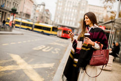Young woman hailing a taxi on the street in the city Royalty Free Stock Images