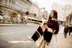 Young woman hailing a taxi on the street in the city. View at young woman hailing a taxi on the street in the city Royalty Free Stock Image