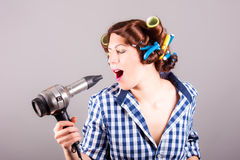 Young woman with hair blower. Portrait of young woman with hair blower royalty free stock photography