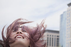 Young woman with hair blowing, looking up, buildings in background Royalty Free Stock Photos