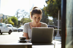 Young woman with hair in a bun using a laptop outside a cafe Stock Photos