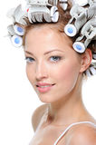 Young woman with hair-curlers Stock Photos
