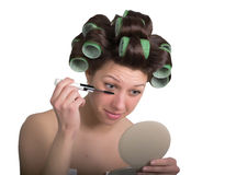 Young woman with hair curlers on the head makes himself make-up. isolated on white background Royalty Free Stock Images