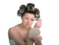 Young woman with hair curlers on the head makes himself make-up. isolated on white background Royalty Free Stock Image