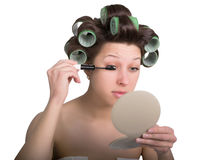 Young woman with hair curlers on the head makes himself make-up. isolated on white background Royalty Free Stock Photos