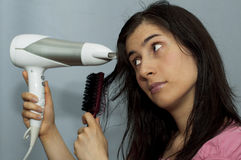 Young woman with hair dryer Stock Image