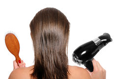 Young woman with a hair dryer and hairbrush Royalty Free Stock Images