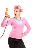 Young woman with hair rollers yelling on a phone Royalty Free Stock Photography