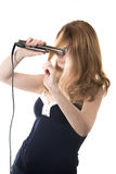 Young woman with hair straightener Stock Photography