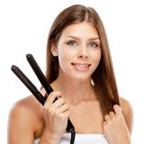 Young woman with a hair straightener Royalty Free Stock Images