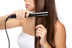 Young woman with a hair straightener. White background Royalty Free Stock Photo
