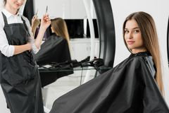 Young woman with hair stylist. Young women with hair stylist in beauty salon Stock Photo