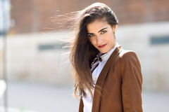 Young woman with hair in the wind in urban background Stock Photo