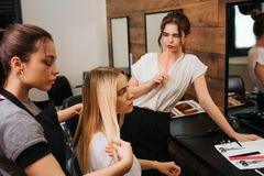 Young woman hairdresser with black apron looking attentively at strand of blonde hair while holding it before. Young women hairdresser with black apron looking stock photos
