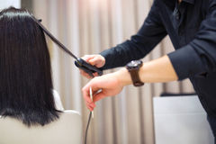 Young woman and hairdresser with hair iron making hairdo. At hair salon Stock Images