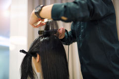 Young woman and hairdresser with hair iron making hairdo. At hair salon Stock Image
