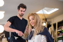 Young woman at hairdresser, making a change in her look stock photography