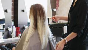A young woman is at the hairdresser`s. A blonde woman is sitting in front of the mirror at the hairdresser`s. The hairdresser is gently brushing woman`s long stock video footage