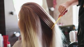 A young woman is at the hairdresser`s. A blonde woman is sitting in front of the mirror at the hairdresser`s. The hairdresser is gently brushing woman`s long stock footage