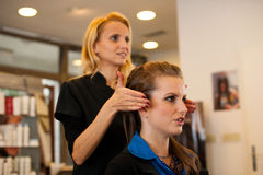 Young woman in hairdresser saloon having a treatment and haircut Stock Photos