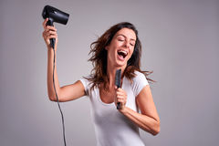 Young woman with a hairdryer stock images