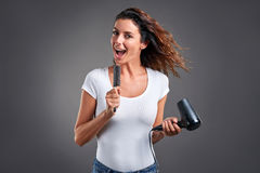 Young woman with a hairdryer Royalty Free Stock Image